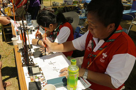 Troop Leaders from the Hong Kong Contingent paint participants names chinese and give them good wishes