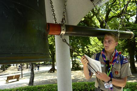 Un participante de la delegacion de USA esta tocando la gran campana situada en el parque de Hiroshima
